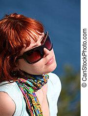 Solar procedures - The woman with red hair enjoys the sun