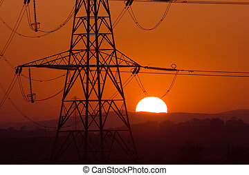 solar pylon - Sun setting behind a silhouetted electricity ...