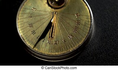 Solar vintage clock rotate. Black background. Close up -...
