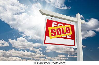 Sold For Sale Real Estate Sign over Clouds and Blue Sky