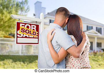 Sold For Sale Sign with Military Couple Looking at House
