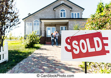 sold house with blurred family on background