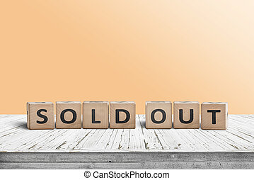 Sold out sign on a wooden table with a yellow wall