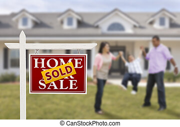 Sold Real Estate Sign and Hispanic Family in Front of House
