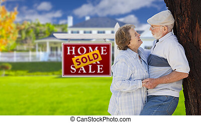 Sold Real Estate Sign with Senior Couple in Front of House