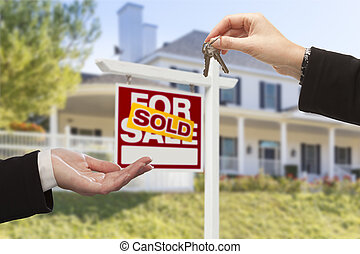 Sold Sign and Agent Handing Over Keys to New Home
