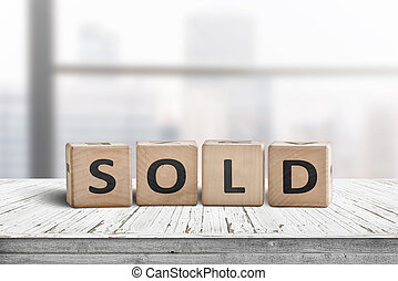 Sold sign on a wooden table