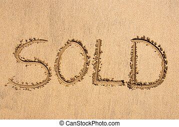 Sold! - The word SOLD written out on a sandy beach
