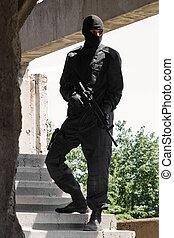 soldado, em, uniforme preto, com, rifle