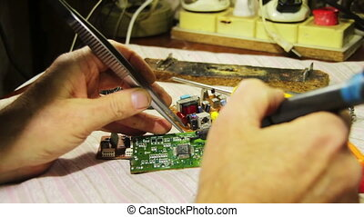 Close-up of male radio engineer working with a soldering iron in his hand, which is the green braze mounting the circuit board with radio components in a laboratory.