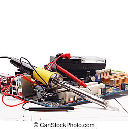 Soldering iron and electronic circuit board on a background of the electric scheme