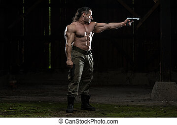 Action Hero Muscled Man Holding A Gun - Standing In Abandoned Building Wearing Green Pants