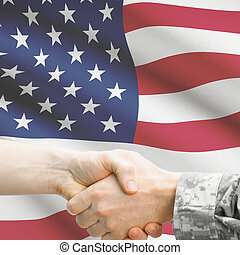 Soldier and doctor shaking hands. Flag on background - United St