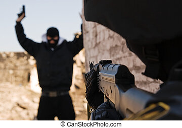 Soldier arresting armed criminal - Military policeman taking...