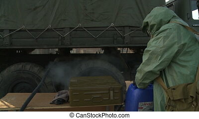 Soldier disinfecting truck - View of military camp