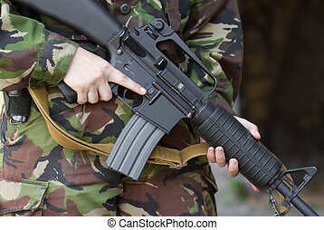 Soldier holding automatic rifle