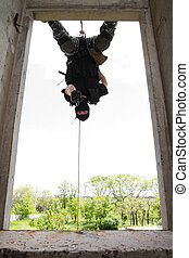 Soldier in black mask hanging on rope with pistol