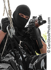 Soldier in black mask hanging on rope with rifle