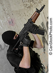 Soldier in black mask moving upstairs with AK-47 rifle