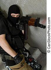Soldier in black mask recharging AK-47 rifle