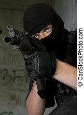 Soldier in black mask targeting with rifle