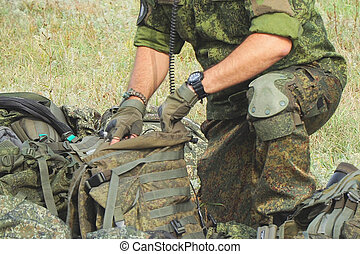 Soldier in camouflage uniform packs backpack