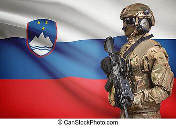 Soldier in helmet holding machine gun with flag on ...