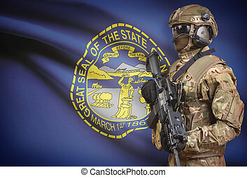 Soldier in helmet holding machine gun with USA state flag on background series - Nebraska