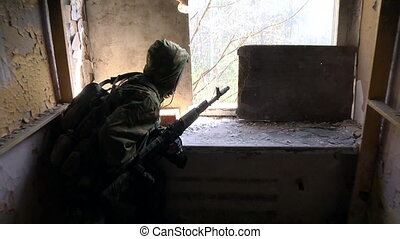 Soldier in military uniform with a weapon is in position in...