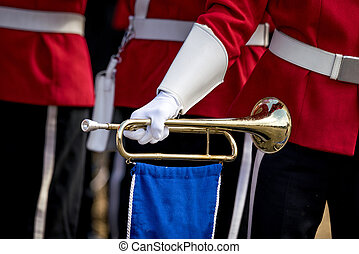 Soldier in red uniform holding a golden trumpet