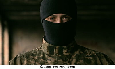 Soldier in uniform and black mask - A man in uniform and a...