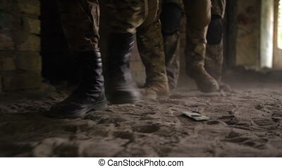 Soldier legs in army combat boots walk in building -...