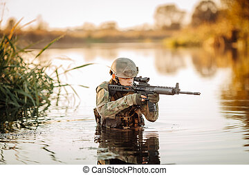 Soldier moving through the water and aiming at the enemy