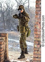 Soldier near wall with a gun