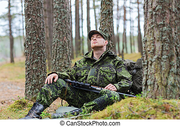 soldier or hunter with gun sleeping in forest - hunting, war...