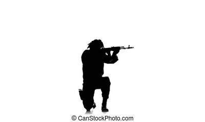 Soldier stands on one knee and aiming a gun. Silhouette -...