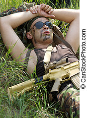 Soldier takes rest lying on a grass