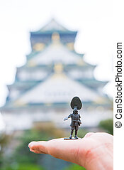 Soldier toy on hand with blurred Osaka Castle as background