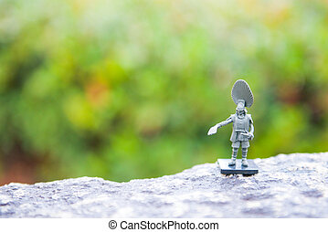 Soldier toy on stone with blurred green background