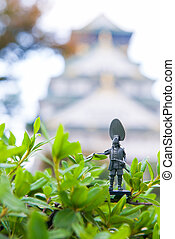 Soldier toy on tree with blurred Osaka Castle as background
