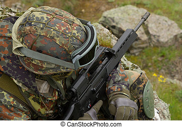 Soldier with a rifle sitting - Soldier in heavy combative...