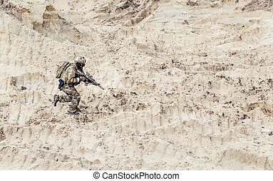 Soldier with carbine running alone through desert