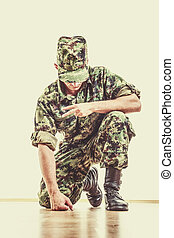 soldier with hidden face in green camouflage uniform and hat kne