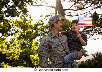 Soldier with son - Front view of a young adult mixed race ...
