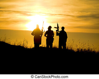 soldiers against a sunset - Silhouettes of several soldiers...