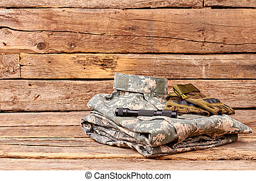 Soldiers camouflage outfit with gloves and flashlight.