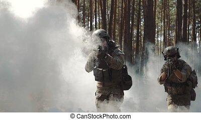 Soldiers come out of the smoke in the forest.