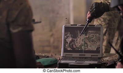 Military men gathering around army laptop and looking at screen displaying map of area while planning capture operation, focus on computer, intelligent satellite technology concept