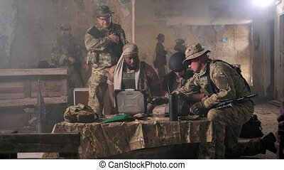 Squad of fighters in camouflage working out plan to detect and capture enemy while gathering around table with army laptop. Group of military men at computer during discussion of intercaption plan