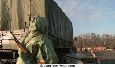 Soldiers disinfecting truck - View of military camp